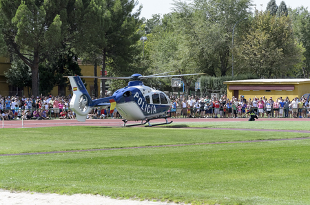 fairs: ALCALA DE HENARES, SPAIN - AUGUST 29th 2015: Unidentified people are watching a helicopter exhibition of spanish police, when its landing, in Alcala de Henares, on August 29th 2015. Army and security corps of Spain have done a show, during the fairs of A