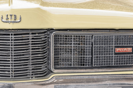 squire: TORREJON DE ARDOZ, SPAIN - OCTOBER 3th 2015: Meeting of classic american cars, during the patronal festivals, by the streets of Torrejon de Ardoz, on October 3th 2015. Partial front view of yellow car, Ford LTD Country Squire of 1969. Editorial