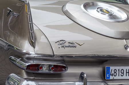 fury: TORREJON DE ARDOZ, SPAIN - OCTOBER 3th 2015: Meeting of classic american cars, during the patronal festivals, by the streets of Torrejon de Ardoz, on October 3th 2015. Partial rear view of champagne color car, Plymouth Fury of 1959.
