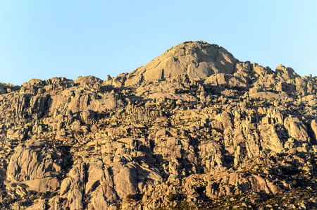 soft peak: Yelmo. Big rock at the top. Its  located in -La Pedriza- (Madrid - Spain), one of the largest granitic ranges of Europe, inside of Guadarrama mountain ranges regional park. Image was taken when Its starting to get dark.