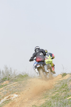 scrambler: GUADALAJARA, SPAIN - FEBRUARY 21th 2016: Spain cross country championship. Two motorcyclists are climbing a slope with their motocross motorbikes, during first race of season 2016, in Guadalajara, on February 21th 2016.