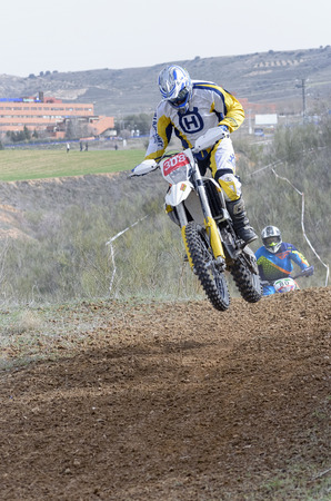 scrambling: GUADALAJARA, SPAIN - FEBRUARY 21th 2016: Spain cross country championship. Motorcyclist is jumping with his motocross motorbike, during first race of season 2016, in Guadalajara, on February 21th 2016.