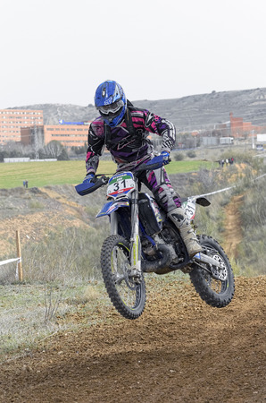 scrambler: GUADALAJARA, SPAIN - FEBRUARY 21th 2016: Spain cross country championship. Motorcyclist is jumping with his motocross motorbike, during first race of season 2016, in Guadalajara, on February 21th 2016.