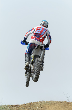 scrambler: GUADALAJARA, SPAIN - FEBRUARY 21th 2016: Spain cross country championship. Back view of motorcyclist is jumping with his motocross motorbike, during first race of season 2016, in Guadalajara, on February 21th 2016.