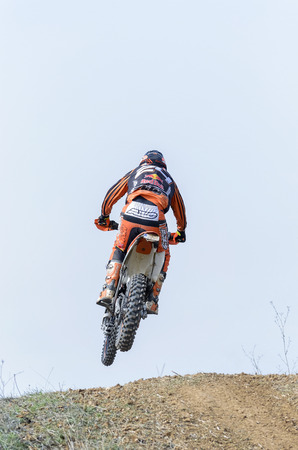 motocross: GUADALAJARA, SPAIN - FEBRUARY 21th 2016: Spain cross country championship. Back view of motorcyclist is jumping with his motocross motorbike, during first race of season 2016, in Guadalajara, on February 21th 2016.