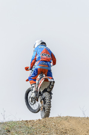 GUADALAJARA, SPAIN - FEBRUARY 21th 2016: Spain cross country championship. Back view of motorcyclist is jumping with his motocross motorbike, during first race of season 2016, in Guadalajara, on February 21th 2016.