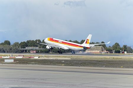 twin engine: MADRID, SPAIN - MARCH 05th 2016: Passenger jet aircraft -Airbus A330-302-, of spanish airliner -Iberia-, is landing over runway, in Madrid Barajas airport (Spain), on March 05th 2016. Photo set: 2 of 2. Editorial