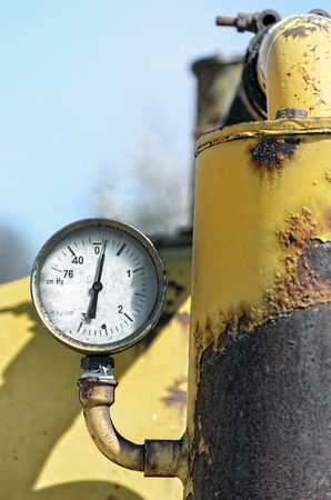 weather gauge: Soft industrial background. Vintage manometer of an old agricultural machine. Metal painted of yellow, with rust produced by many years at outdoor.