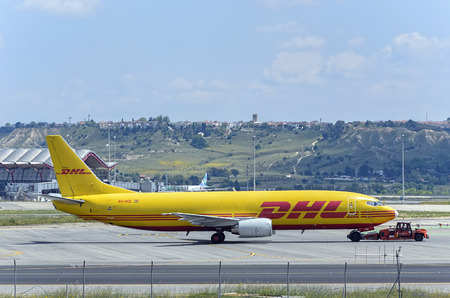 towed: MADRID, SPAIN - MAY 15th 2016: Cargo aircraft -Boeing 737-, of -Air Ghana DHL- airline, being towed by a tug tractor, in Madrid-Barajas -Adolfo Suarez- airport, on May 15th 2016. Editorial