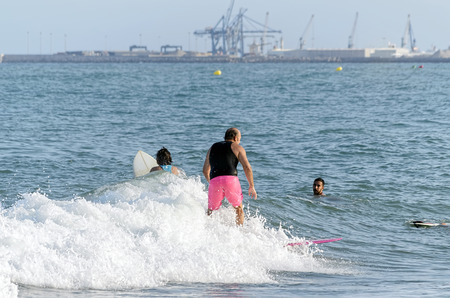 surfers paradise: CASTELLON, SPAIN - AUGUST 1th 2016: Three surfers riding or trying to catch a wave with their surfboards, in the beach of Castellon de la Plana, on August 1th 2016.