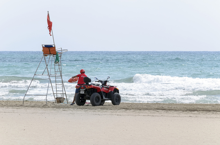 CASTELLON, SPAIN - AUGUST 1th 2016: Observation post. Lifeguard boss with -Can-Am Outlander 400- four-wheeled motorcycle. Red flag. Prohibition of swim, at the beach of Castellon de la Plana (Spain), on August 1th 2016.