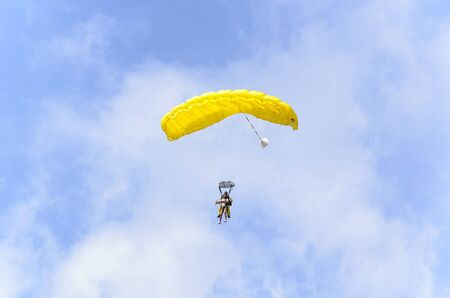 CASTELLON, SPAIN - AUGUST 1th 2016: Summer vacations. Couple, an instructor and a man, flying in parachute, over the airfield of Castellon de la Plana (Spain), on August 1th 2016. Sunny day with clouds.