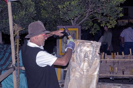 trinchante: ALCALA DE HENARES, ESPAÑA - 8vo DE OCTUBRE DE 2016: Carver de madera está haciendo una escultura de Miguel de Cervantes, durante el mercado de Cervantino, en la ciudad de Alcalá de Henares, el 8 de octubre de 2016. Editorial