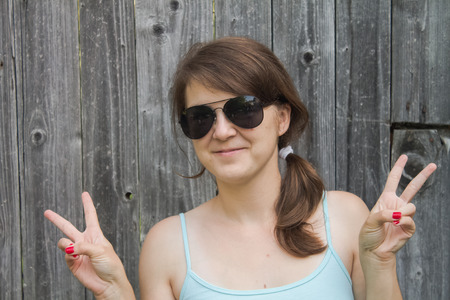 Happy young woman showing peace gesture with two hands , with red nails, wearing sunglasess looking at camera with charming smile. Standing against wooden background.
