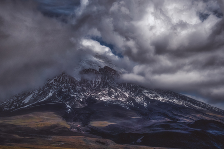 Picturesque mountain landscape with steep mountain peak covered with snow under dense dark clouds