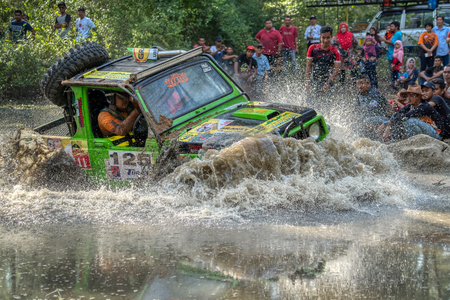 KELANTAN, MALAYSIA - NOVEMBER 2018 : 4x4 vehicle driving at speed through water watched by a group of spectators while competing in the Rainforest Challenge, Kelantan, Malaysia