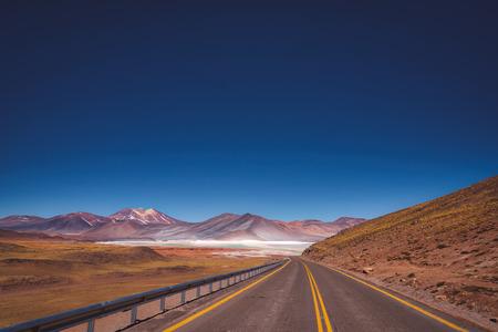 Asphalt road through the Atacama desert, Chile leading towards distant mountains and salt pans
