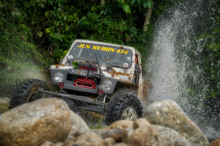 KELANTAN, MALAYSIA - NOVEMBER 2018 : 4x4 vehicle driving in the Rainforest Challenge in Kelantan, Malaysia crossing through a spray of water onto large boulders and rocks