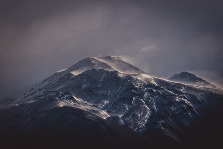 Cold grey clouds over a rugged mountain with snow in an atmospheric winter landscape in South America