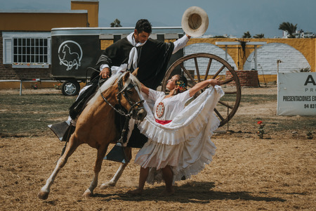TRUJILLO, PERU - SEPTEMBER 2018 : Peruvian woman in traditional white carnival dress dancing with cowboy riding a horse and holding his hat, during outdoor performance