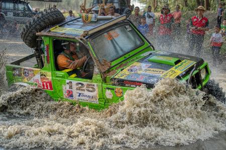 KELANTAN, MALAYSIA - NOVEMBER 2018 : Spectators watching a 4x4 vehicle in the Rainforest Challenge in Kelantan, Malaysia as it drives through deep water