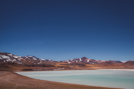 Salty lake in desert landscape with brown mountains covered with snow. Andes, Chile