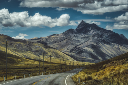 Tarred valley through the Peruvian highlands with tall mountain peaks and deep valley