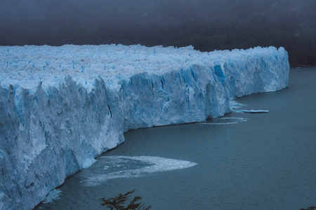 Shards of ice calving off the face of a glacier splashing into the water below in Patagonia, Argentina