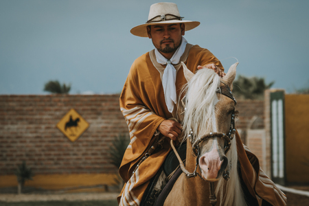 TRUJILLO, PERU - SEPTEMBER 2018 : Bearded man Peruvian cowboy riding a horse, viewed in close-up from his front with copy space Stock fotó - 117050164