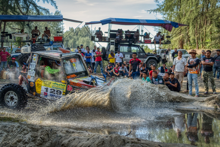 KELANTAN, MALAYSIA - NOVEMBER 2018 : 4x4 vehicle entering water at speed in a cloud of spray watched by a group of spectators while competing in the Rainforest Challenge in Kelantan, Malaysia