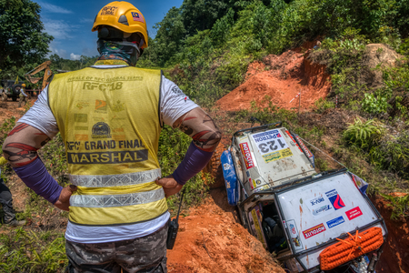 KELANTAN, MALAYSIA - NOVEMBER 2018 : 4x4 vehicle negotiating a steep gully and incline while competing in the Rainforest Challenge, Kelantan, Malaysia watched by a competitor or official