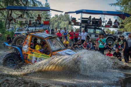 KELANTAN, MALAYSIA - NOVEMBER 2018 : Spectators watching the Rainforest Challenge, Kelantan, Malaysia as a 4x4 vehicle negotiates a water hazard in a cloud of spray