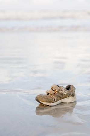 stranded: Stranded children sport shoe on the beach Stock Photo
