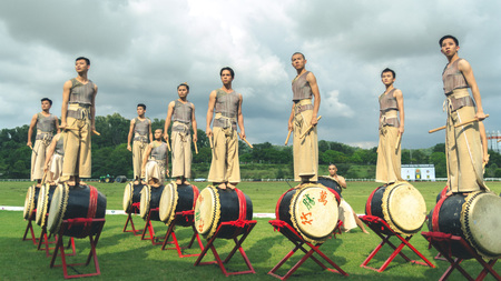 chinese drum: Putrajaya, Malaysia - Circa November, 2015: Traditional chinese drum player standing on top of their drums during break time performance at Malaysia Open Polo event field. Soft focus due to wide aperture. Editorial