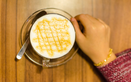 Woman hand reaching a cup of hot caramel coffee macchiato. Selective focus on white foam. Wood background. Shallow DOF.