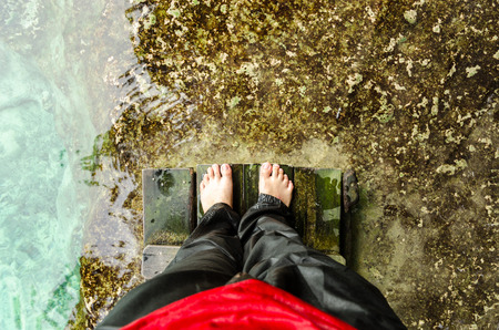 High angle view of feet at the edge of tropical emerald pool in Krabi, Thailand. Soft focus on feet.