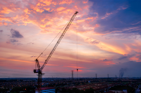 Hoisting tower crane at construction site with sunset cloud background and housing estate. Standard-Bild