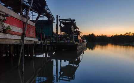 Calm blue hour sunset at fisherman village and woodenboat with reflection on the water. Soft focus due to long exposure. Standard-Bild