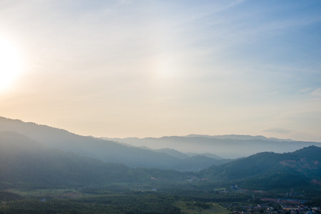 View of foggy sunrise shining behind mountain from Bukit Broga, Selangor. It is a tourist attraction to hike especially on weekends.