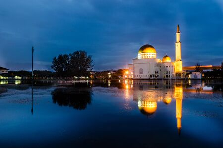 Blue hour sunrise at floating mosque with reflection on the water lake. Standard-Bild