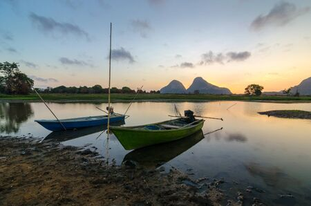 Boat tied on the lakeside during magical sunrise with moving clouds and reflection on the water. Mountain background.