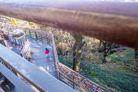 Small child walking happily on the walking platform at Namsan Tower, Seoul. Famous love locks hanging along the hand rail.