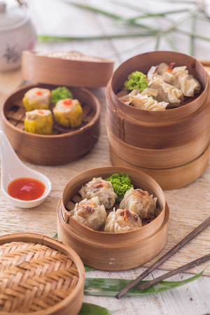 Soft and delicious shrimp shumai dimsum in stacked bamboo steamer for snack or tea break. Lit by natural light on white wood table and cloth.