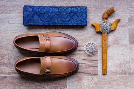 Flat lay shot of traditional accecories for groom in malay wedding ceremony. Consist of keris or malay dagger, belt and shoes. Standard-Bild