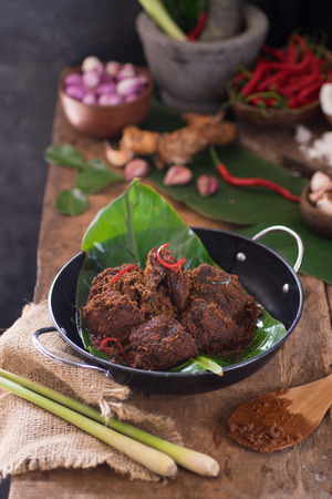 Rendang is a traditional dish shared from Malaysia and Indonesia, commonly served during eid celebration. Made of coconut milk, meat, and spices. Served in wok on wooden table.