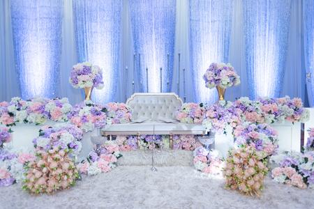 花嫁と花婿が伝統的な服装で座っているマレーの結婚式で上げられたステージ。それは通常、人工花で重く飾られています。