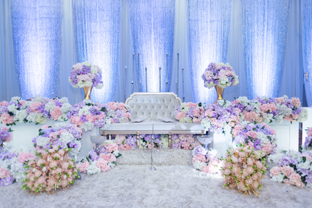 A raised stage in malay wedding where the bride and bridegroom sits in a traditional attire. it is usually decorated heavily with artificial flower. 스톡 콘텐츠