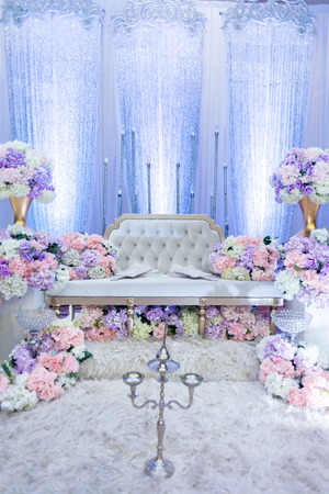 A raised stage in malay wedding where the bride and bridegroom sits in a traditional attire. it is usually decorated heavily with artificial flower. Reklamní fotografie