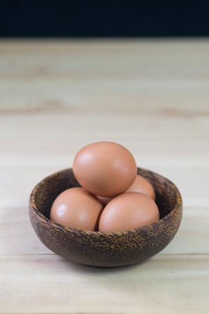 Fresh poultry egg inside bowl on wooded table by the window with copy space. Lit by natural light.