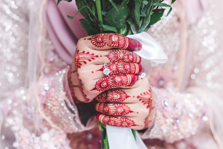 Close up shot on happy bride holding hand bouquet showing big diamond ring before celebration. Hands decorated with henna.